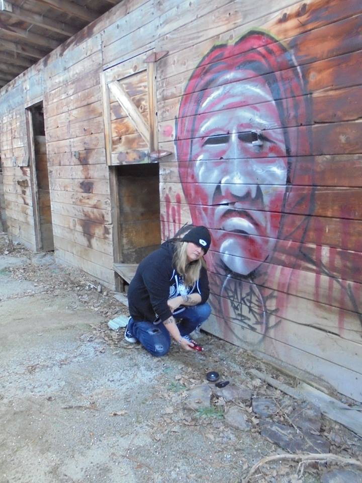 Michelle Le Baron in front of the Native American graffiti piece in the old stables in Verdi, Nevada.