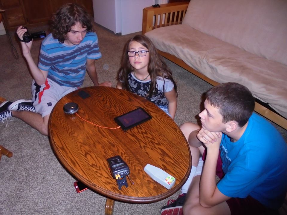 Aaron, Aaleah, and Grayson Austin in a lodge across from the Gold Hill Hotel learning about ghost hunting gadgets.